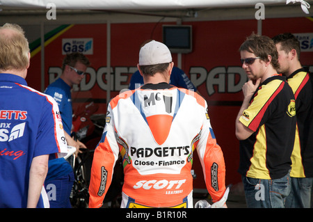 John McGuinness chats to his pit crew prior to a practice session for the 2008 Isle of Man TT races. - Stock Photo