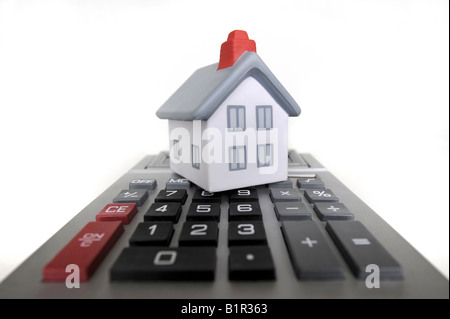 MODEL HOUSE WITH CALCULATOR RE HOUSING COSTS/BILLS/ECONOMY/MARKET - Stock Photo