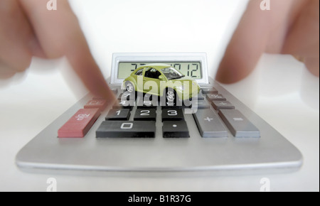 MODEL CAR ON CALCULATOR RE MOTORING COSTS REPAIRS HOUSEHOLD BUDGETS ETC UK - Stock Photo