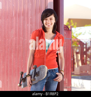 Teen girl with skateboard hangs out at the park - Stock Photo