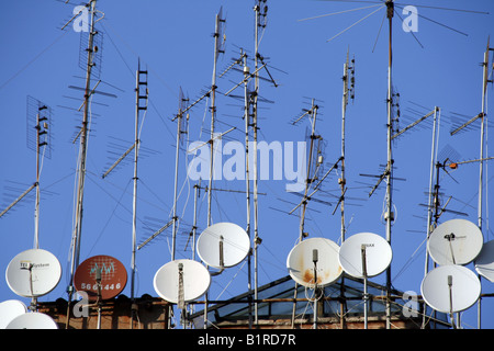tv aerials and satellite dishes on rooftop - Stock Photo