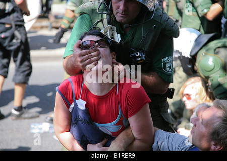 Police officer covering a demonstrator's mouth and nose during the clearing of a sit-in blockade against a neo-Nazi - Stock Photo