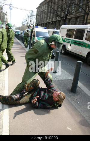 Police officer threatening a punk lying on the ground with his fist, Berlin, Germany, Europe - Stock Photo