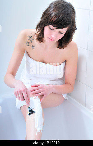 Young beautiful brunette, dressed with a towel, shaving her legs in the bathroom - Stock Photo