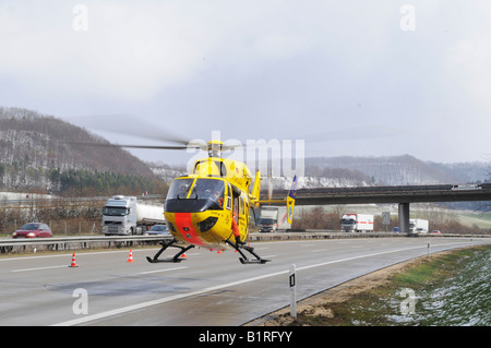 The ADAC German auto club air rescue helicopter Christoph 22 taking off to hospital from autobahn or motorway A8 - Stock Photo