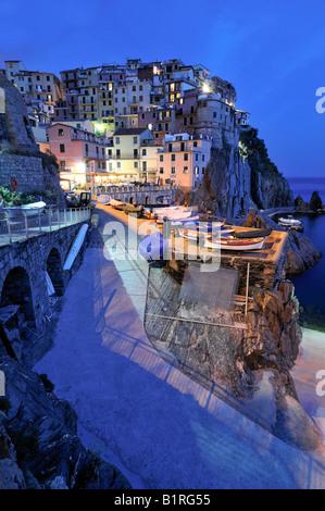 Village of Manarola nestled atop steep coastline at dusk, Liguria, Cinque Terre, Italy, Europe - Stock Photo