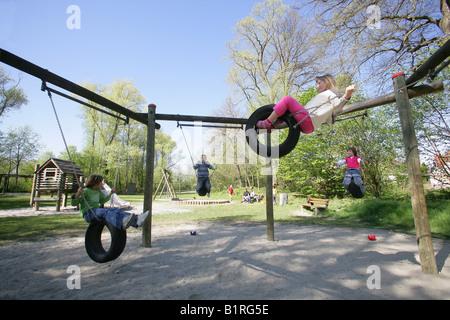 Children swinging on car tire swings at a playground in Muehldorf am Inn, Upper Bavaria, Bavaria, Germany, Europe - Stock Photo