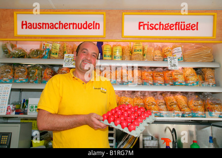 Poultry vendor holding a carton of dyed eggs, weekly farmer's market in Muehldorf am Inn, Upper Bavaria, Germany, - Stock Photo