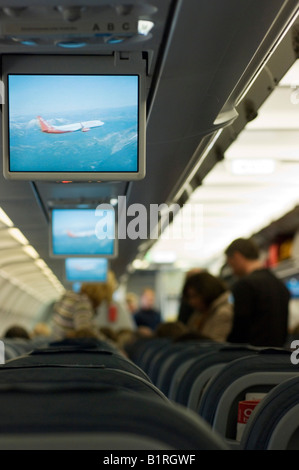 Passengers looking for their seats in the aeroplane before departure, storing their hand luggage - Stock Photo