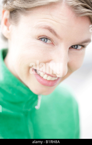 Close-up, woman wearing a green jacket looking into the camera - Stock Photo