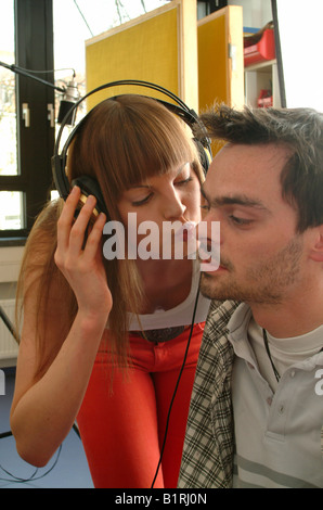 Young woman wearing headphones kissing her sound engineer on the cheek - Stock Photo
