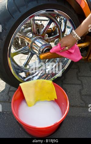Woman washing a motorcycle - Stock Photo