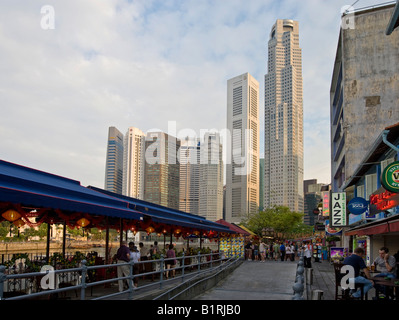 Numerous restaurants at Boat Quay on the shores of the Singapore River in front of the high-rise buildings of Singapore's - Stock Photo