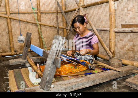 Woman weaving textiles in the traditional way at an old loom, Tete Batu, Lesser Sunda Islands, Indonesia, Asia - Stock Photo
