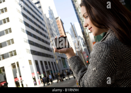 A young woman is located in a downtown city area carrying a hand held computerized device. - Stock Photo