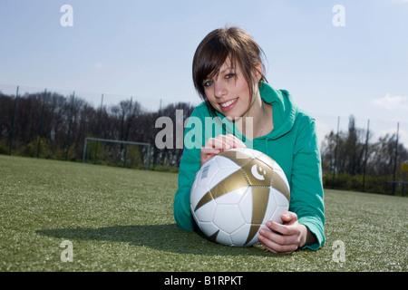 Young woman lying with a football in front of her on a football pitch - Stock Photo