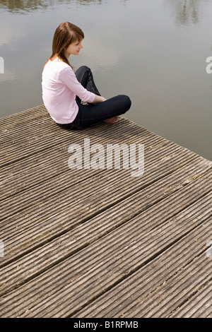 Young woman sitting on a jetty, wooden dock, looking at the water - Stock Photo