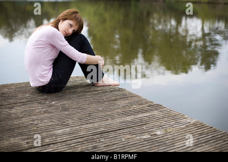 Young woman sitting on a jetty, wooden dock, looking pensive - Stock Photo