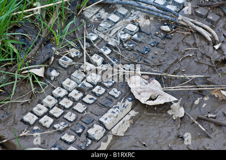 Computer keyboard covered in mud