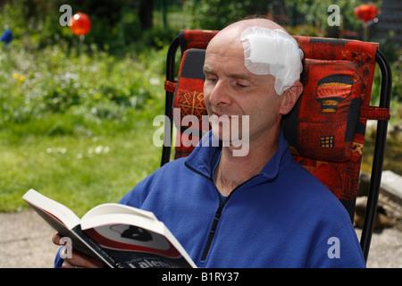 Man, 45, with an adhesive bandage on his head, sitting in a garden chair reading a book, Geretsried, Bavaria, Germany, - Stock Photo