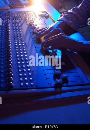 Hands of a sound engineer adjusting the regulators of a professional mixer unit - Stock Photo