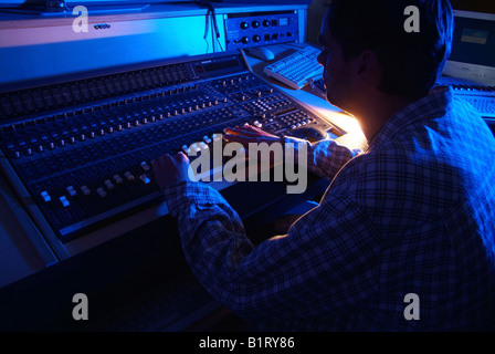 Sound engineer working on a mixer unit of a recording studio - Stock Photo