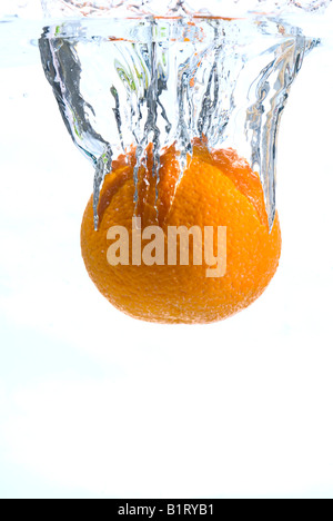 Orange plunging into water - Stock Photo