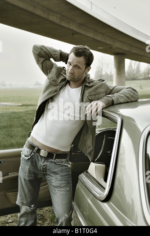 31-year-old man dressed up as James Dean, leaning against a car - Stock Photo