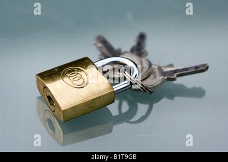 Brass padlock and three keys, ideal to lock up and secure items of value - Stock Photo