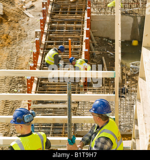 builders at work on construction site - Stock Photo