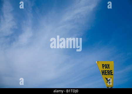 'Pay here' car park sign again blue sky and white clouds for pay and display car park in England UK GB British Isles - Stock Photo