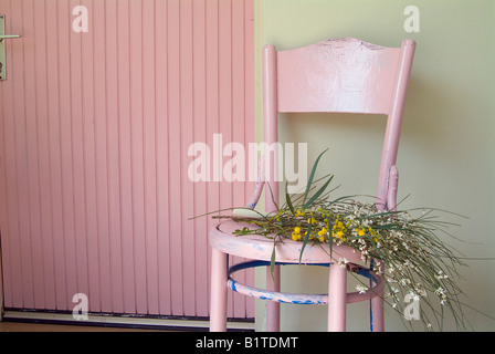 old pink chair and flowers in front of green wall and pink door - Stock Photo