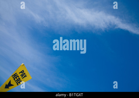 'Pay here' car park sign again blue sky white clouds for pay and display car park in England UK GB British Isles - Stock Photo