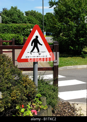 Red Triangle featuring a figure of a walking man on  safety crossing sign on British Road - Stock Photo