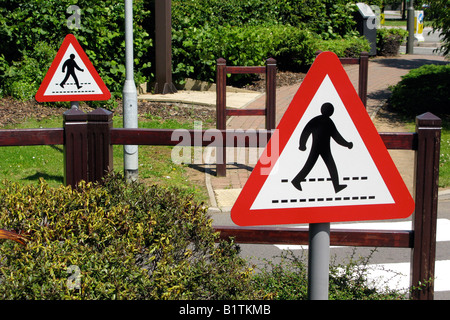 Red Triangle featuring a figure of a walking man on  safety crossing signs on British Road - Stock Photo