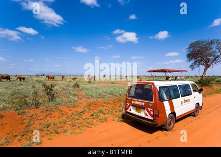 Tourists in a safari bus watching family of African Bush Elephants in savannah Tsavo East National Park Coast Kenya - Stock Photo