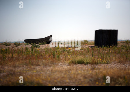 Clinker built boat, wasting away on shingle beach. - Stock Photo