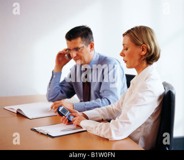 man and woman with mobile phone at business meeting - Stock Photo
