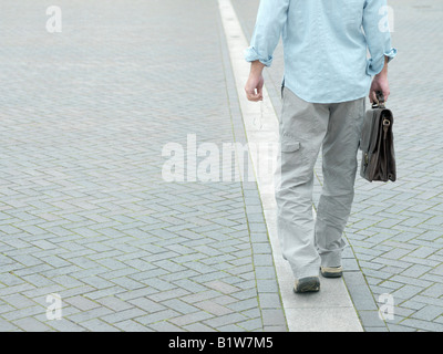 man walking along white line - Stock Photo