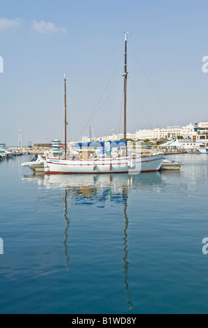 A reflected view of a yacht moored in the Yasmine Hammamet marina on a sunny day with blue sky. - Stock Photo