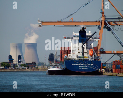 Container ship in the port of Antwerp Belgium with Doel nuclear reactor in the background - Stock Photo