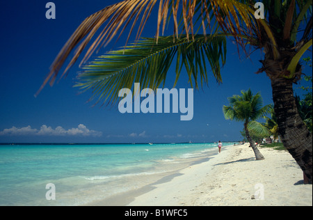 WEST INDIES Jamaica Negril Sandy stretch of beach beside flat aquamarine water with woman walking along shoreline - Stock Photo