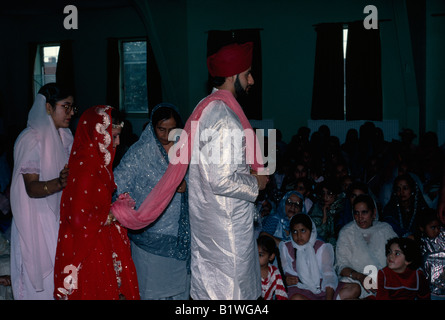 ENGLAND Religion Sikhism Bride and groom at Sikh wedding ceremony walk around the altar and holy scriptures four - Stock Photo