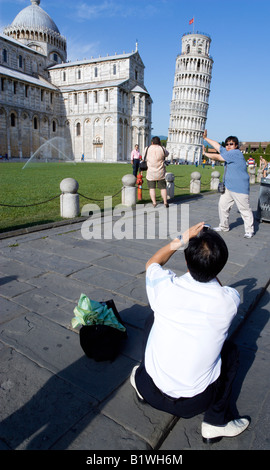 ITALY Tuscany Pisa Asian tourists take photo pretending to hold up Leaning Bell Tower by Duomo Cathedral in Field - Stock Photo