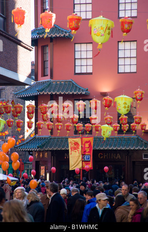 ENGLAND London Chinatown people in Wardour Street walk beneath red and yellow paper lanterns for Chinese New Year - Stock Photo