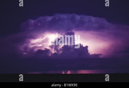 Sheet and flash lightning during a distant electric thunderstorm seen at night in northern Kenya East Africa - Stock Photo