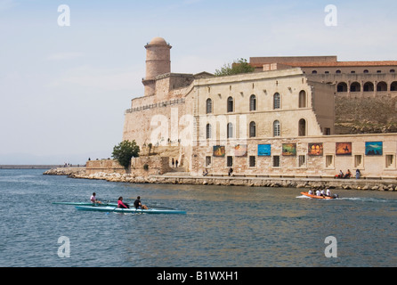 Marseille harbour entrance showing Fort St. Jean with an outdoor exhibition of paintings on the walls. - Stock Photo