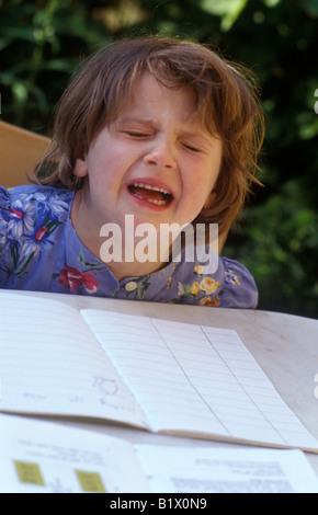 little girl doing her homework and having a tantrum - Stock Photo