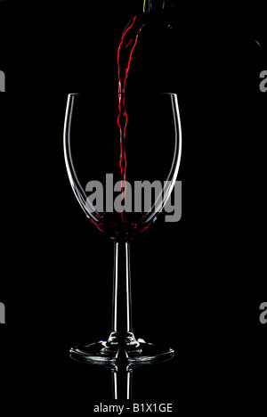 Low key shot of red wine being poured into a glass against a black background Stock Photo