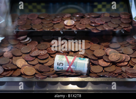 A five pound note prize in a penny falls machine at an amusement arcade. - Stock Photo